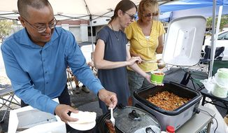ADVANCE FOR USE MONDAY, AUG. 14, 2017, AND THEREAFTER- In this Aug. 5, 2017, photo, Stone Soup members Tony Penton, Gabrielle Hastings and Christine Popp help serve food to anyone looking for a meal and some conversation in Fond du Lac, Wis. Stone Soup sets up every Saturday in the Fond du Lac Library parking lot. (Doug Raflik/The Reporter via AP)