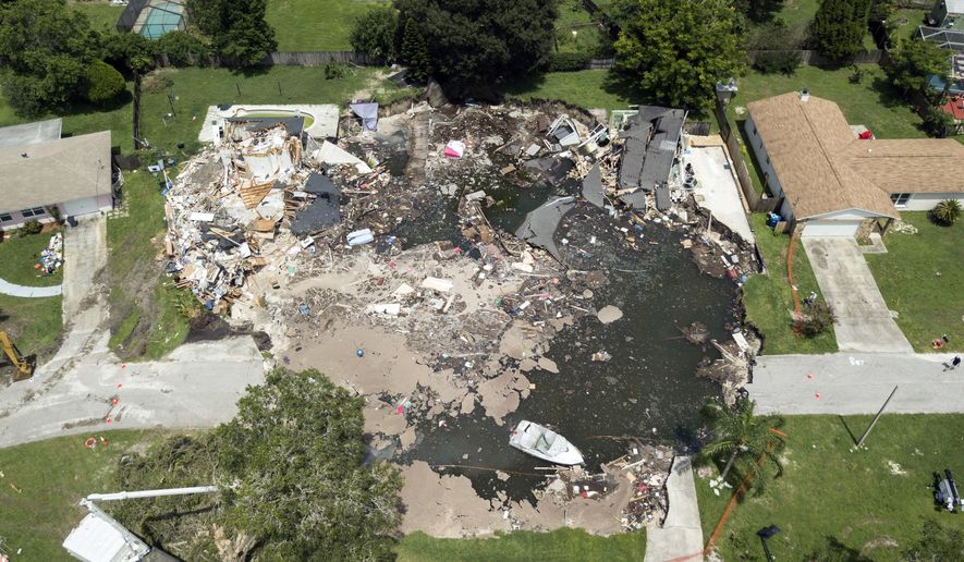 FILE - This Friday, Aug. 4, 2017 file photo shows a large sinkhole in the Lake Padgett Estates community in Land O' Lakes, Fla. Florida officials say more homes could possibly be condemned due to a massive sinkhole that has already made seven homes unlivable, including two that were consumed entirely by the collapsing hole. The sinkhole opened July 14. It now stretched about 260 feet at its widest point. (Luis Santana Tampa Bay Times via AP, File)