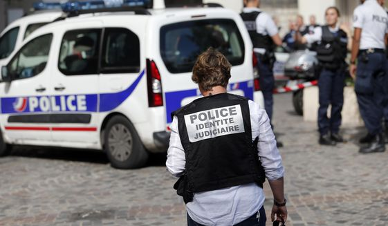French Police work on the scene where French soldiers were hit and injured by a vehicle in the western Paris suburb of Levallois-Perret near Paris, France, Wednesday, Aug. 9, 2017. French police are searching for a driver who slammed his BMW into a group of soldiers, injuring six of them in an apparent ambush before speeding away, officials said. The incident in Levallois, northwest of Paris, is the latest of several attacks targeting security forces in France.(AP Photo/Kamil Zihnioglu)