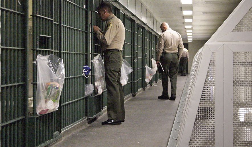 FILE - In this Oct. 3, 2012, file photo, Los Angeles County Sheriff's deputies inspect a cell block at the Men's Central Jail in downtown Los Angeles. The largest sheriff's department in the U.S. uses unsound methods to compile data about violence in Los Angeles County jails and provided inaccurate statistics about jailhouse assaults to news organizations and its oversight agency, according to a report released Wednesday Aug. 9, 2017. (AP Photo/Reed Saxon, File)