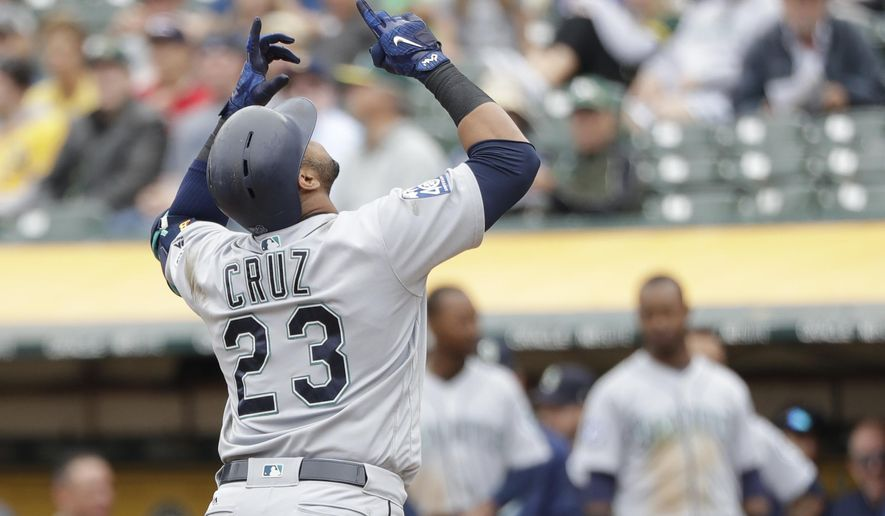 Seattle Mariners' Nelson Cruz points skyward as he crosses home plate following his solo home run against the Oakland Athletics during the fifth inning of a baseball game Wednesday, Aug. 9, 2017, in Oakland, Calif. (AP Photo/Marcio Jose Sanchez)