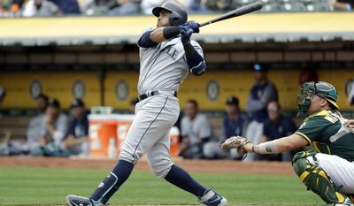 Seattle Mariners' Nelson Cruz follows through on his two-run home run against the Oakland Athletics during the third inning of a baseball game Wednesday, Aug. 9, 2017, in Oakland, Calif. (AP Photo/Marcio Jose Sanchez)