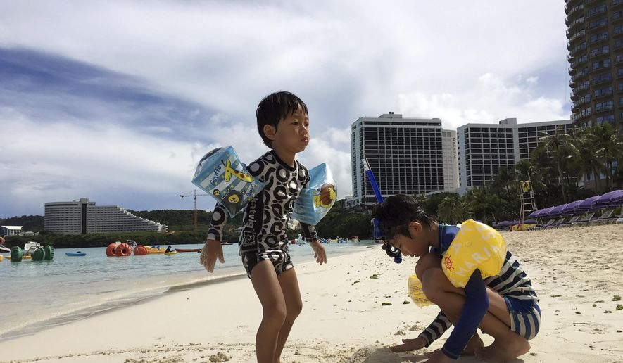 """Kids play in the sand in Tumon, Guam on Thursday, Aug. 10, 2017. The small U.S. territory of Guam has become a focal point after North Korea's army threatened to use ballistic missiles to create an """"enveloping fire"""" around the island. The exclamation came after President Donald Trump warned Pyongyang of """"fire and fury like the world has never seen."""" (AP Photo/Tassanee Vejpongsa)"""