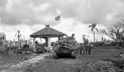 """FILE - This August 1944 file photo shows an American flag atop the first U.S. tank to lead the push to Agana, capital of Guam. The small U.S. territory of Guam has become a focal point after North Korea's army threatened to use ballistic missiles to create an """"enveloping fire"""" around the island. The exclamation came after President Donald Trump warned Pyongyang of """"fire and fury like the world has never seen"""" on Tuesday, Aug. 8, 2017. (AP Photo/Joe Rosenthal, File)"""