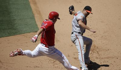 Los Angeles Angels' Mike Trout, left, safely takes first base beating the throw to Baltimore Orioles starting pitcher Kevin Gausman during the fifth inning of a baseball game, Wednesday, Aug. 9, 2017, in Anaheim, Calif. (AP Photo/Jae C. Hong)