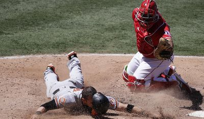 Baltimore Orioles' Craig Gentry, left, loses his helmet after he was tagged out by Los Angeles Angels catcher Juan Graterol while trying to score on a single hit by Jonathan Schoop during the sixth inning of a baseball game, Wednesday, Aug. 9, 2017, in Anaheim, Calif. (AP Photo/Jae C. Hong)