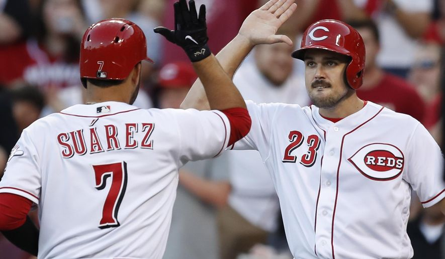 Cincinnati Reds' Eugenio Suarez (7) celebrates with Adam Duvall (23) after hitting a two-run home run off San Diego Padres starting pitcher Travis Wood during the third inning of a baseball game, Wednesday, Aug. 9, 2017, in Cincinnati. (AP Photo/John Minchillo)