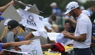 Dustin Johnson signs autographs after a practice round at the PGA Championship golf tournament at the Quail Hollow Club Thursday, April 13, 2017, in Charlotte, N.C. (AP Photo/John Bazemore)