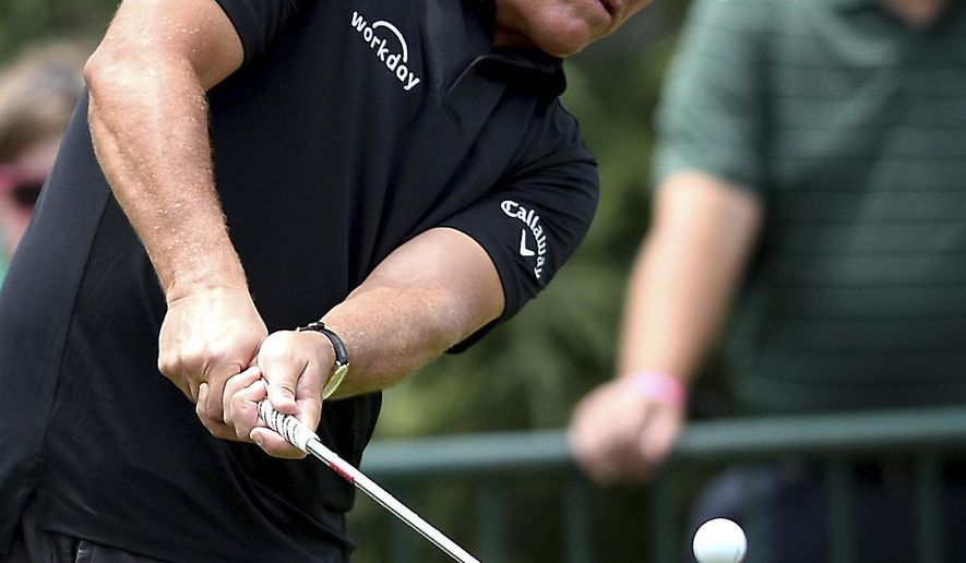 Phil Mickelson watches the flight of his ball during practice for the PGA Championship golf tournament at Quail Hollow Club in Charlotte, N.C., Monday, Aug. 7, 2017. (Jeff Siner/The Charlotte Observer via AP)