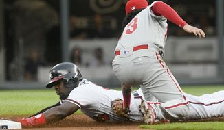 Atlanta Braves' Brandon Phillips is caught stealing at second base as Philadelphia Phillies shortstop Freddy Galvis makes the tag to end the first inning of a baseball game, Wednesday, Aug. 9, 2017, in Atlanta. (AP Photo/John Amis)