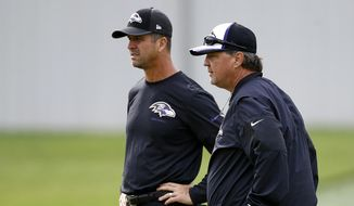 Baltimore Ravens offensive coordinator/quarterbacks coach Marty Mornhinweg, right, walks past head coach John Harbaugh during an NFL football training camp practice in Owings Mills, Md., Tuesday, Aug. 8, 2017. (AP Photo/Patrick Semansky)