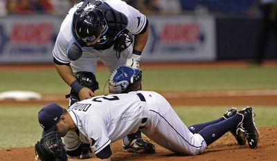 Tampa Bay Rays catcher Wilson Ramos, top, talks to starter Jake Odorizzi as he tries to stand after he was hit by a line drive from Boston Red Sox's Eduardo Nunez during the fifth inning of a baseball game Wednesday, Aug. 9, 2017, in St. Petersburg, Fla. (AP Photo/Steve Nesius)