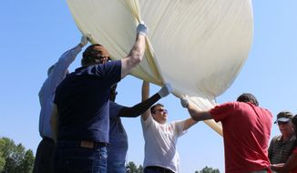Students and faculty, including Mark Iewicz, center, a mechanical engineering student, prepare to test launch a camera-carrying balloon at the University of Hartford in West Hartford, Conn. on Wednesday, Aug. 9,2017. The team from the University of Bridgeport and the University of Hartford are part a project that will send cameras into the stratosphere to photograph this month's solar eclipse. (AP Photo/Pat Eaton-Robb)