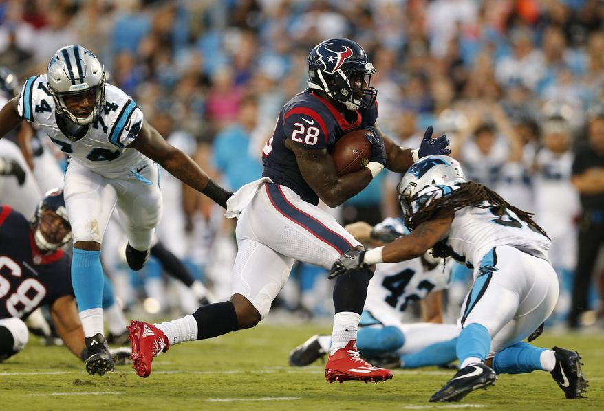 Houston Texans running back Alfred Blue (28) runs against Carolina Panthers defensive back Dezmen Southward (37) and Carolina Panthers defensive end Daeshon Hall (74) during the first half of an NFL preseason football game, Wednesday, Aug. 9, 2017, in Charlotte, N.C. (AP Photo/Jason E. Miczek)