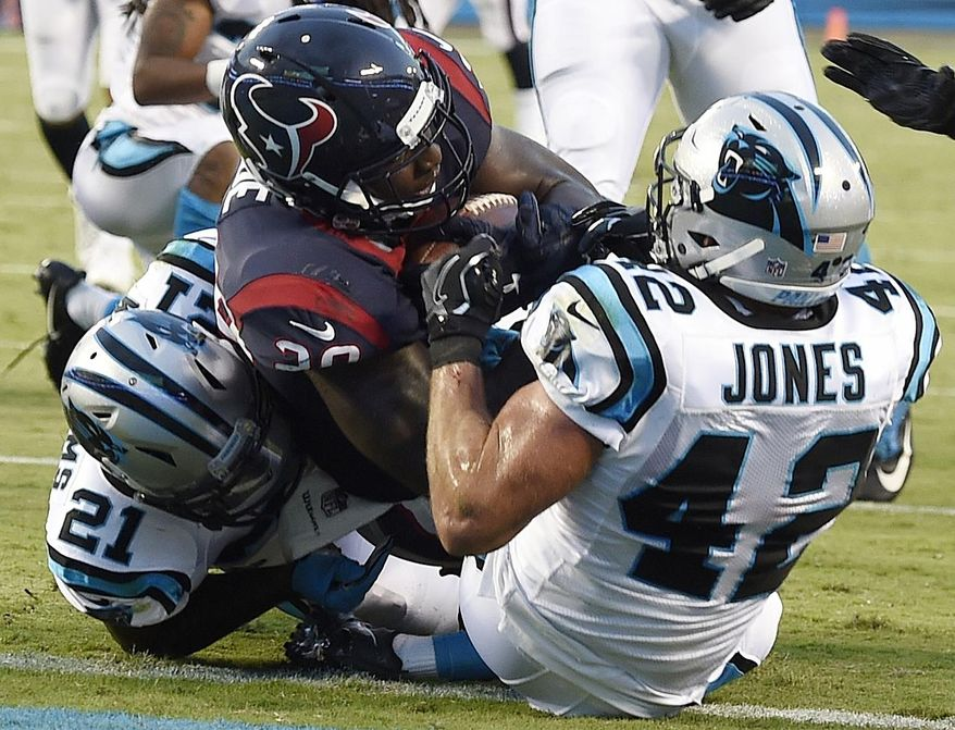 Houston Texans running back Alfred Blue (28) is tackled in the end zone by Carolina Panthers free safety Colin Jones (42) and Carolina Panthers defensive back Teddy Williams (21) during the first half of an NFL preseason football game, Wednesday, Aug. 9, 2017, in Charlotte, N.C. (AP Photo/Mike McCarn)