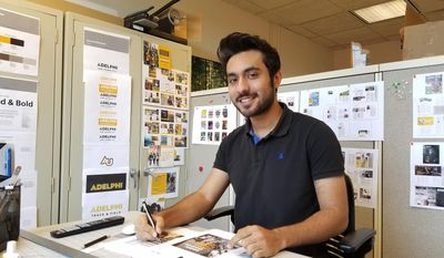 In this undated photo provided by Adelphi University, student Usman Anwar works at his campus job on Long Island, N.Y. Anwar said he skipped a trip home to Pakistan this summer because he worried he might not be allowed to re-enter the U.S. if he left. Like Anwar, some international students have remained in the U.S. because they worried about potential travel troubles, even if they aren't from majority Muslim countries in the government's travel ban rules. (Noelle Fiallo-Evans/Adelphi University via AP)