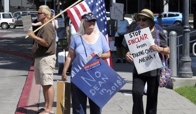 FILE - In this Aug. 8, 2017, file photo, Paula Povilaitis, center, holds a sign that reads ''No Dean in 2018'' during a protest outside the office of U.S. Sen. Dean Heller, R-Nev., in Reno, Nev. News that Heller will face a primary challenge next year came as a surprise to many of the more than 50 mostly Democrats protesting outside his Reno office where they rally weekly against the Trump administration and Heller's changing position on health care. (AP Photo/Scott Sonner, File)
