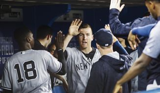 New York Yankees' Todd Frazier is congratulated by teammates after scoring against the Toronto Blue Jays during the fifth inning of a baseball game in Toronto, Wednesday, Aug. 9, 2017. (Mark Blinch/The Canadian Press via AP)