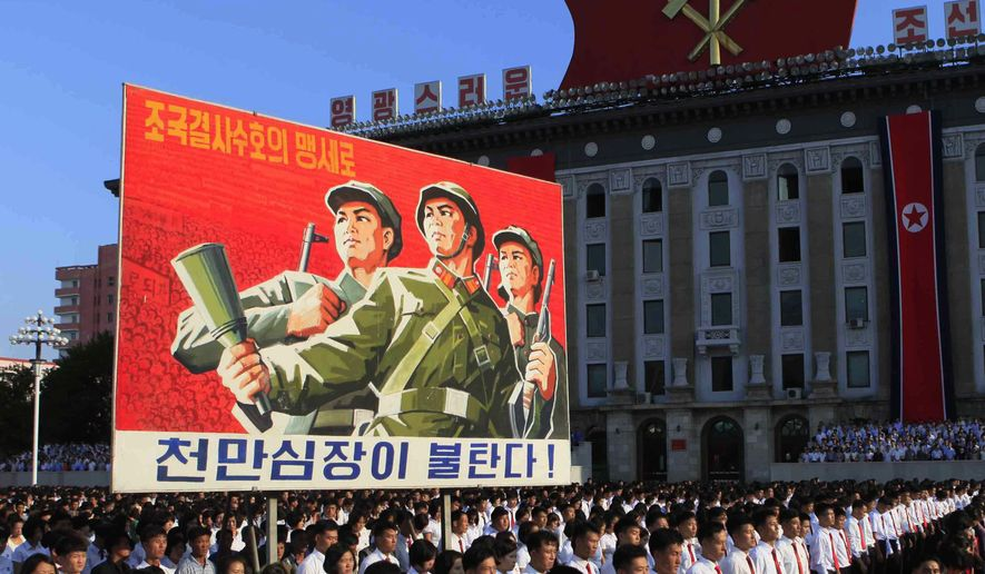 """Tens of thousands of North Koreans gathered for a rally at Kim Il Sung Square carrying placards and propaganda slogans as a show of support for their rejection of the United Nations' latest round of sanctions on Wednesday Aug. 9, 2017, in Pyongyang, North Korea. Sign says, """"Protect our nation to the death"""" and """"Hearts of 10 million people are burning."""" (AP Photo/Jon Chol Jin)"""