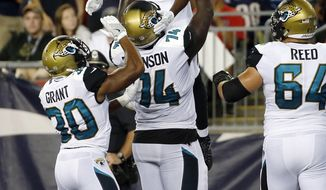 Jacksonville Jaguars wide receiver Dede Westbrook, top, celebrates his touchdown catch with teammates Corey Grant, left, Cam Robinson, center, and Chris Reed, right, in the second half of an NFL preseason football game against the New England Patriots, Thursday, Aug. 10, 2017, in Foxborough, Mass. (AP Photo/Mary Schwalm)