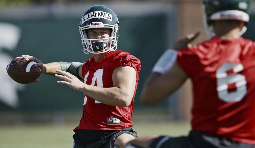 FILE- In a July 31, 2017, file photo, Michigan State quarterback Brian Lewerke (14) warms up during NCAA college football practice in East Lansing, Mich. Lewerke is the favorite to take over as the starting quarterback. He appeared in four games in 2016 before a season-ending broken leg. (Mike Mulholland/The Ann Arbor News via AP, File)