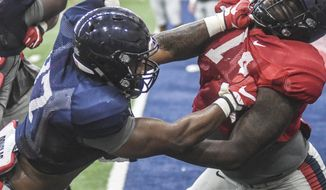 Mississippi defensive lineman Qaadir Sheppard (97), left, and offensive lineman Greg Little (74) square off during an NCAA college football practice in Oxford, Miss., on Monday, Aug. 7, 2017. (Bruce Newman, The Oxford Eagle via AP)