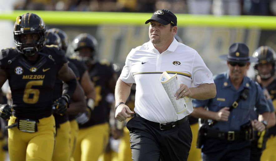 FILE - In this Oct. 29, 2016, file photo, Missouri head coach Barry Odom jogs out with his team before the start of an NCAA college football game against Kentucky in Columbia, Mo. (AP Photo/Jeff Roberson, File)