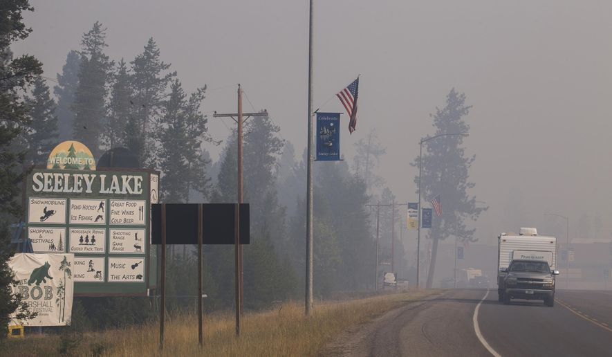 In this photo provided by the U.S. Forest Service a pickup truck pulls a camper through the wildfire smoke in Seeley Lake in Missoula County, Mont., on Thursday, Aug. 10, 2017. Health officials in western Montana are strongly recommending residents of Seeley Lake leave town due to hazardous smoke from area wildfires. (Kari Greer/U.S. Forest Service via AP)