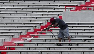 With a little over three weeks until the season-opening NCAA college football game against Arkansas State, a worker pressure-washes the seats at Memorial Stadium in Lincoln, Neb., Thursday, Aug. 10, 2017. (AP Photo/Nati Harnik)
