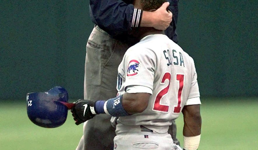FILE - In this Aug. 29, 1997, file photo, mpire Ken Kaiser gives Chicago Cubs runner Sammy Sosa a hug after calling him out on an attempted steal of second base during the first inning of a baseball game against the Cleveland Indians at Jacobs Field in Cleveland. Kaiser, a former major league umpire, died in his hometown of Rochester, N.Y., on Tuesday, Aug. 8, the World Umpires Association said, Thursday, Aug. 10, 2017. He was 72. Kaiser was a colorful figure in more than two decades on the diamond. His career abruptly ended nearly two decades ago during labor talks. He joined a group of umpires who submitted resignations in 1999 during negotiations. The gamble by the Major League Umpires Association failed and he was not rehired.  (AP Photo/Mark Duncan, File)