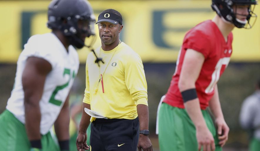 FILE - In this April 5,2017, file photo, Oregon's first year head coach Willie Taggart watches his running back Royce Freeman, left, quarterback Justin Herbert as they run through a drill during the first day of spring practice for the Ducks in Eugene, Ore. (Andy Nelson/The Register-Guard via AP, File)