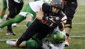 FILE - In this Nov. 26, 2016, file photo, Oregon State running back Ryan Nall, top, dives over Oregon's Danny Mattingly for a touchdown in the second half an NCAA college football game in Corvallis, Ore. (AP Photo/Timothy J. Gonzalez, File)