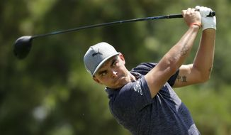 Rickie Fowler watches his tee shot on the third hole during the first round of the PGA Championship golf tournament at the Quail Hollow Club Thursday, Aug. 10, 2017, in Charlotte, N.C. (AP Photo/Chuck Burton)