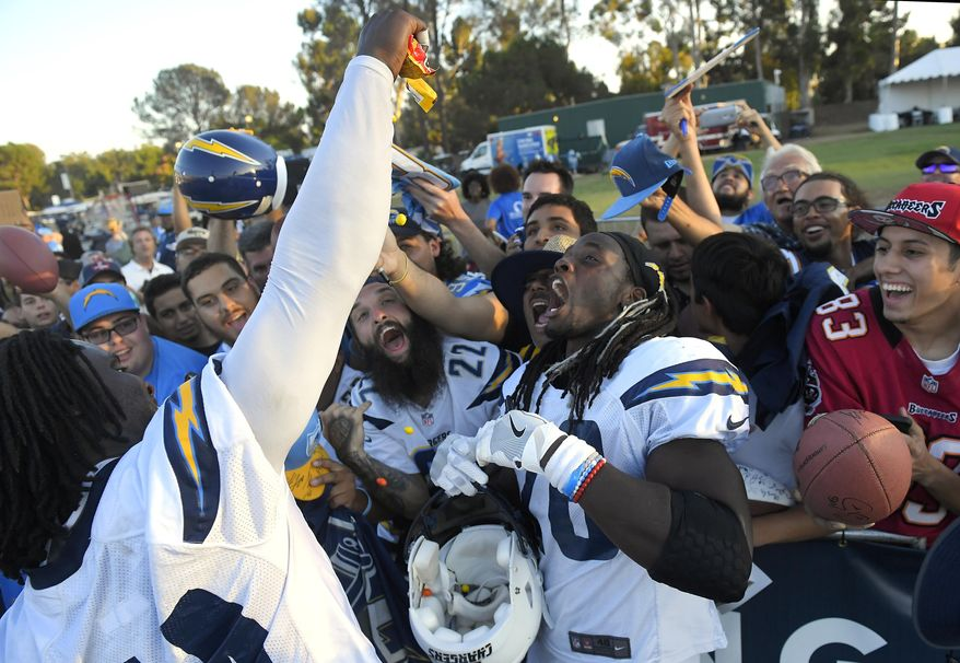 Los Angeles Chargers defensive end Melvin Ingram, left, pours candy over fans and running back Melvin Gordon during a joint NFL football practice with the Los Angeles Rams, Wednesday, Aug. 9, 2017, in Irvine, Calif. (AP Photo/Mark J. Terrill)