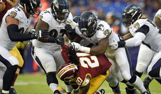 Washington Redskins running back Rob Kelley (20) is tackeld by a group of Baltimore Ravens defenders in the first half of a preseason NFL football game, Thursday, Aug. 10, 2017, in Baltimore. (AP Photo/Nick Wass)