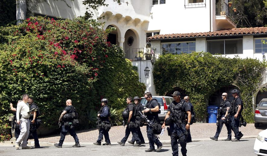 Authorities leave a home in Pacific Palisades in Los Angeles Thursday, Aug. 10, 2017. A gunman was found dead Thursday inside a huge Los Angeles home following a standoff in which he fired several rounds at the woman who lives there during a domestic argument, police said. (AP Photo/Damian Dovarganes)
