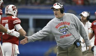 FILE - In this Jan. 2, 2017, file photo, Wisconsin head coach Paul Chryst congratulates his players after a touchdown during the first quarter of the Cotton Bowl NCAA college football game against Western Michigan,in Arlington, Texas. Wisconsin was 10-3 last year, beating Western Michigan in the Cotton Bowl. Chryst figures to have another strong team this season. (AP Photo/LM Otero, File