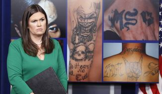 White House press secretary Sarah Huckabee Sanders stands in front of pictures of MS-13 gang tattoos during a press briefing at the White House in Washington, Thursday, July 27, 2017. (AP Photo/Alex Brandon)