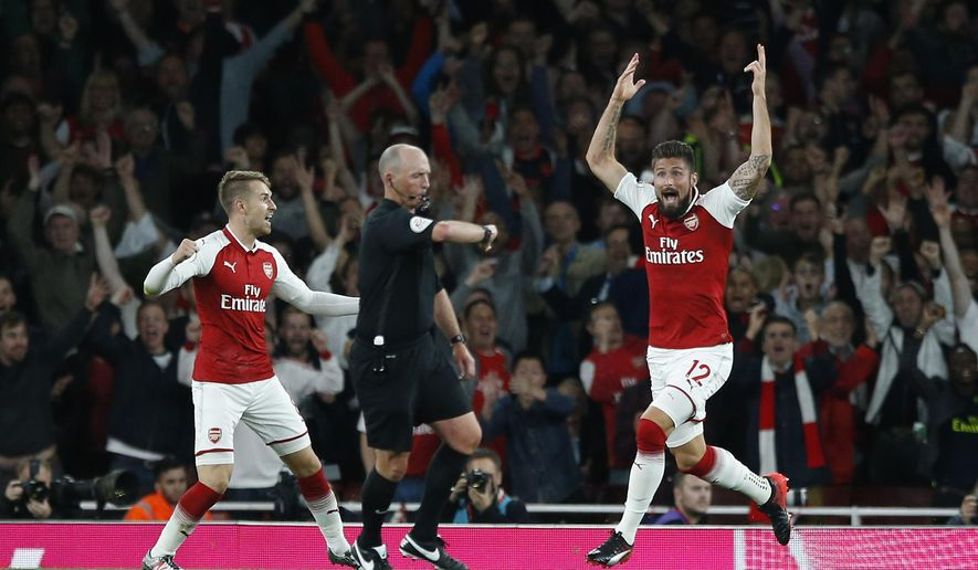 Arsenal's Olivier Giroud reacts as and celebrates as referee Mike Dean, centre, says the ball has crossed the line for a goal during their English Premier League soccer match between Arsenal and Leicester City at the Emirates stadium in London, Friday, Aug. 11, 2017. Arsenal won the match 4-3.(AP Photo/Alastair Grant)