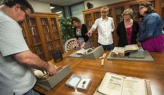 In this July 16, 2017 photo, Adam Hooks, associate professor of English from the University  of Iowa, points out several books from the time of poet and playwright William Shakespeare during Shakespearience at Illinois State University's Milner Library Special Collections room, in Normal, Ill. The room houses a handful of rare items, including books from Shakespeare's time. Those items were featured at Shakespearience along with several other rare and fine books during a program that gave visitors a rare glimpse into Shakespeare's world. (Lewis Marien/The Pantagraph via AP)