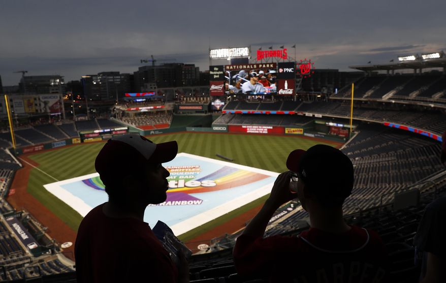 Daniel Baker, left, and Taylor Triggs, of Arlington, Va., wait under the concourse during a rain delay of a baseball game between the San Francisco Giants and the Washington Nationals, Friday, Aug. 11, 2017, in Washington. (AP Photo/Carolyn Kaster)