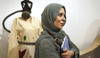 "Narges Mousavi an Iranian artist and daughter of Mir Hossein Mousavi stands during her exhibition in ""House of Free Designers"" art gallery in Tehran, Iran, Friday, Aug. 11, 2017. The daughter of Iran's opposition leader Mir Hossein Mousavi, who has been under house arrest since early 2011, is holding a painting exhibition in Tehran. (AP Photo/Ebrahim Noroozi)"