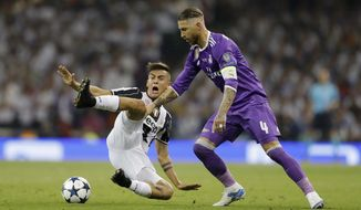 FILE - In this photo taken on June 3, 2017, Real Madrid's Sergio Ramos, right, challenges Juventus' Paulo Dybala during the Champions League final soccer match between Juventus and Real Madrid at the Millennium stadium in Cardiff, Wales. After a tumultuous two months, Juventus is looking to get back to what it does best: winning trophies. (AP Photo/Frank Augstein)