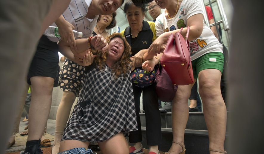 FILE - In this July 29, 2016, file photo, a woman cries while demonstrating with relatives of passengers aboard Malaysia Airlines Flight 370 outside the Ministry of Foreign Affairs in Beijing. U.S. seabed exploration company Ocean Infinity said on Friday, Aug. 11, 2017, it had offered to take the financial risk of a renewed search for the missing Malaysian airliner, as victims' families urged the Malaysian government to agree to a private-sector hunt for Flight 370's wreckage. (AP Photo/Mark Schiefelbein, File)