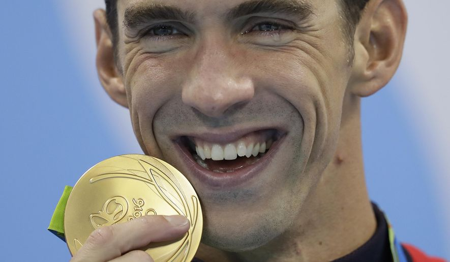 FILE - In this Aug. 9, 2016, file photo, United States' Michael Phelps has tears in his eyes as he shows off his gold medal after the men's 200-meter butterfly final at the 2016 Summer Olympics in Rio de Janeiro, Brazil. In terms of medals, no one come close to the Baltimore Bullet. (AP Photo/Michael Sohn, File)