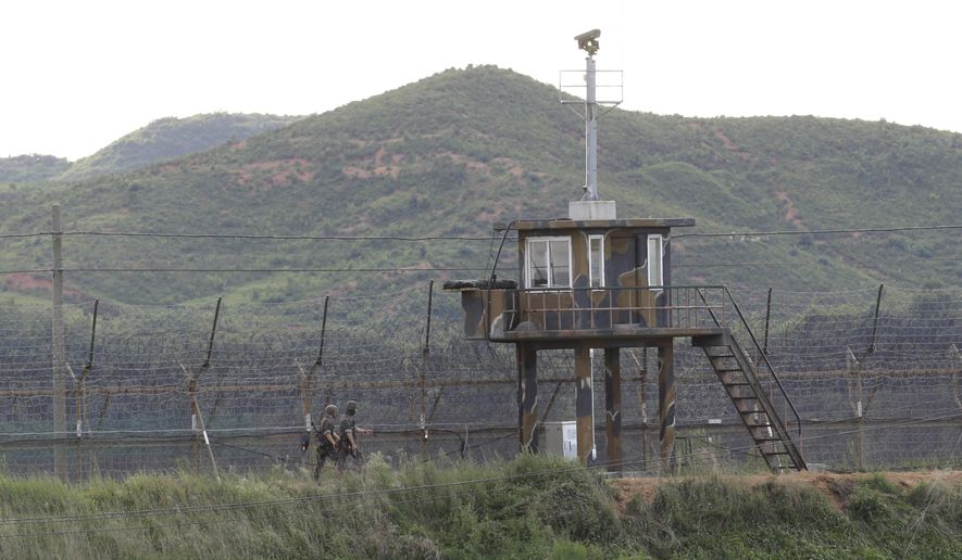South Korean army soldiers patrol along the barbed-wire fence in South Korea's Paju near the border with North Korea, Friday, Aug. 11, 2017. Military officials said Friday they plan to move ahead with large-scale U.S.-South Korea exercises later this month that North Korea, now finalizing plans to launch a salvo of missiles toward Guam, claims are a rehearsal for war. (AP Photo/Ahn Young-joon)