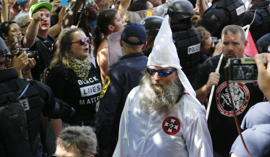 This July 8, 2017, photo shows members of the KKK escorted by police past a large group of protesters during a KKK rally in Charlottesville, Va. (AP Photo/Steve Helber) ** FILE **