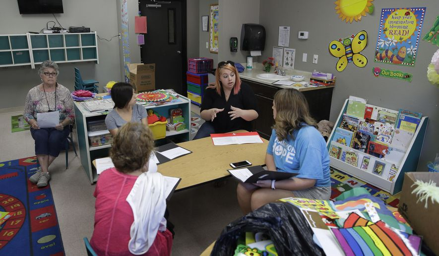 In this photo taken Aug. 8, 2017, Kelsey Nellis, second from right, instructs employees in preparation for the start of the school year at the Mountain View Christian Schools in Las Vegas. More than a third of U.S. states have created school voucher programs that bypass thorny constitutional and political issues by turning them over to non-profits that rely primarily on businesses to fund them. But the programs are raising questions about transparency and accountability at a time when supporters are urging that it be expanded into a federal program. (AP Photo/John Locher)