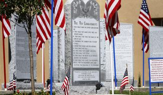 FILE - This Aug. 28, 2014 file photo shows the Ten Commandments monument at the Bloomfield, N.M., Municipal Complex. A coalition of nearly two dozen states led by Texas Attorney General Ken Paxton is stepping into a dispute in northwestern New Mexico over the monument. Paxton and attorneys general from 22 other states are supporting city leaders in Bloomfield, who are asking the U.S. Supreme Court to hear their appeal of a lower court ruling that requires the removal of the display from the lawn outside City Hall, Thursday, Aug. 10, 2017. (Jon Austria/The Daily Times via AP, File)