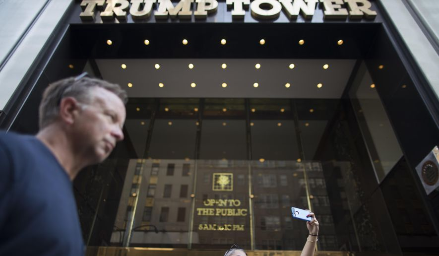 In this Thursday, Aug. 10, 2017 photo, a couple takes a selfie outside Trump Tower in New York.  Donald Trump plans to come home to Trump Tower for a few days starting Sunday, the first time since his inauguration. New York City police are planning a slight security clampdown in the area around the skyscraper for the duration of his visit. (AP Photo/Mary Altaffer)